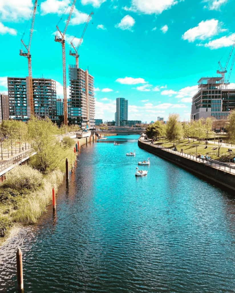 Visitors enjoy the banks of Queen Elizabeth Olympic Park in Canary Wharf.